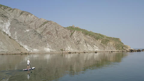 Lone sup surfer slowly moves along calm blue water along rocky shore to large boulders. Mountain Footage