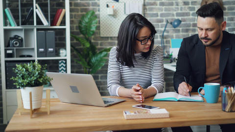 Girl and guy discussing business ideas strategy writing in notebook in office Footage