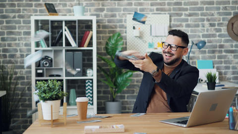 Excited guy throwing money laughing enjoying wealth in office alone Live Action