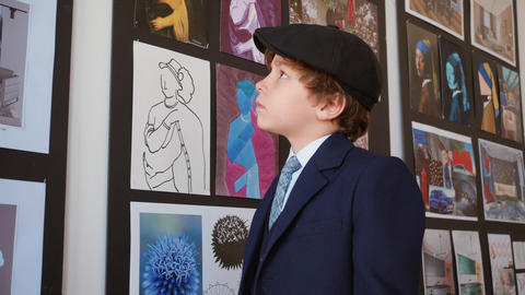 Little boy watching picture in art gallery. Young boy looking art picture in Footage