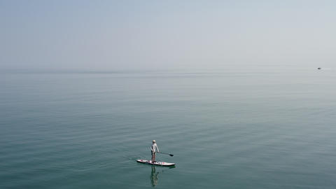 Calm seascape. Man moving on sup board. Surfer moving to shore and coastal rocks. Boats floating on Live Action