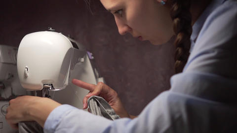A woman sews clothes on a sewing machine by the light of a lamp. Fashion Live Action