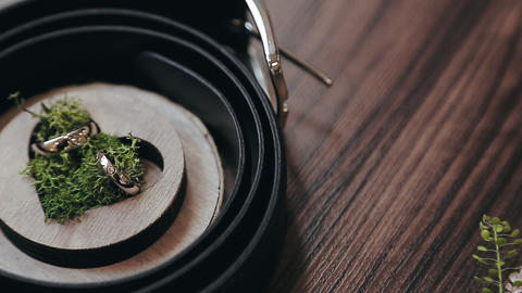 Wedding rings in a wooden box in the shape of a heart filled with moss. Wedding Footage