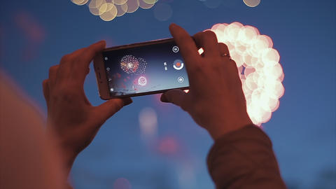 Girl shooting fireworks on the smartphone. Woman shoots salute on the phone Footage