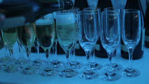 A waiter pours champagne into glasses at a club party Footage