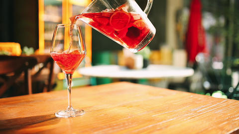 Woman hand pouring red rose wine cocktail from jug to glass. This alcoholic red wine cocktail is Live Action