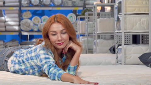 Happy beautiful woman lying on a new orthopedic mattress at furnishings store Live Action