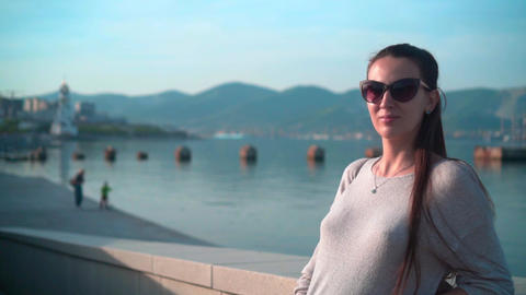 Young charming girl in sunglasses in clear summer weather. A girl stands on the Footage