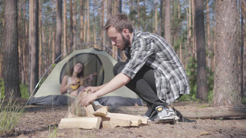 The young man kindling a fire in the foreground in the forest while pretty young Live Action