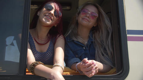 Two young woman is smile and watch to you from auto trailer window Vacation to Footage