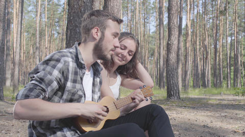 Portrait handsome bearded young man playing ukulele while pretty young happy Live Action