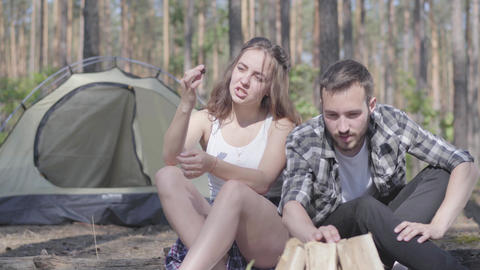 Portrait young man kindling a fire in the forest while adorable young woman Live Action