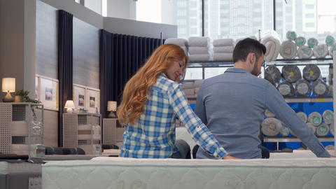 Cheerful couple smiling to the camera, while choosing new bed at furniture store Footage
