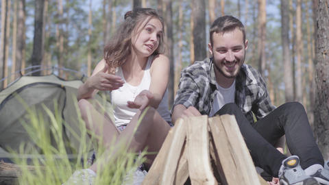 Portrait handsome young man kindling a fire in the forest while beautiful young Live Action