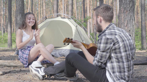 The young man playing ukulele at the tent while pretty young woman sitting in Live Action