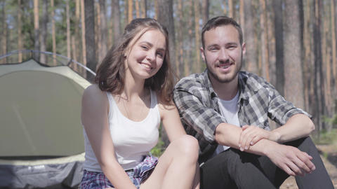 Portrait of handsome bearded young man and pretty young happy woman sitting near Live Action