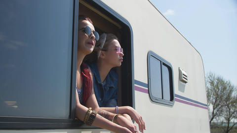 Two young woman is dancing and watch to nature frome auto trailer window Footage