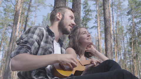Portrait attractive bearded young man playing ukulele while pretty young happy Footage