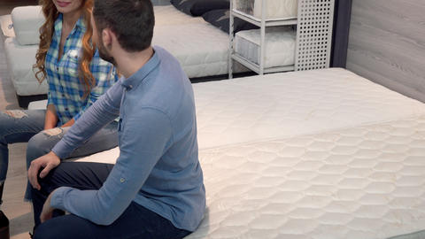 Lovely happy couple lying on comfortable othopedic mattress at furniture shop Footage