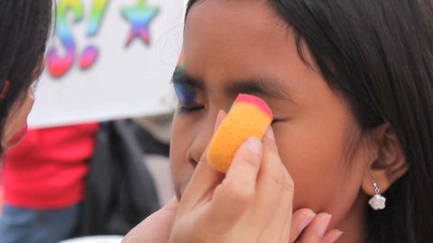 Asian Girl Getting A Rainbow Face Painting Mask Applied Stock Video Footage