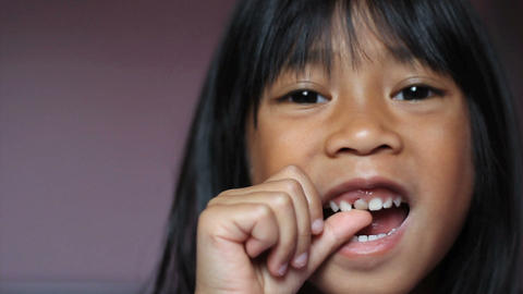 Asian Girl Wiggling Her First Loose Tooth Close Up Footage