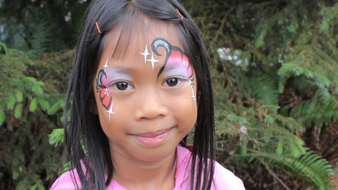 Cute Asian Girl Showing Off Her Face Paint Design Footage
