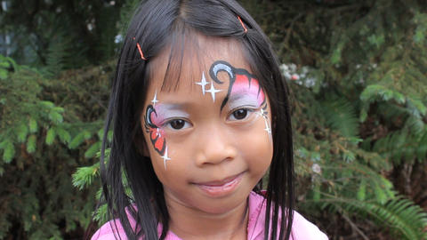 Cute Asian Girl Showing Off Her Face Paint Design Stock Video Footage