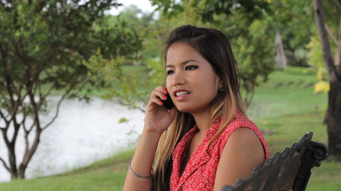 Asian Girl Answers Cell Phone By The Lake Stock Video Footage