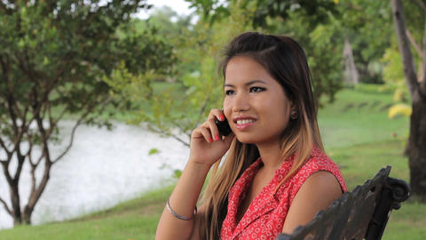 Asian Girl Answers Cell Phone By The Lake stock footage