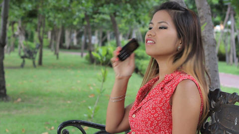 Attractive Asian Girl Answers Cell Phone In The Park Stock Video Footage