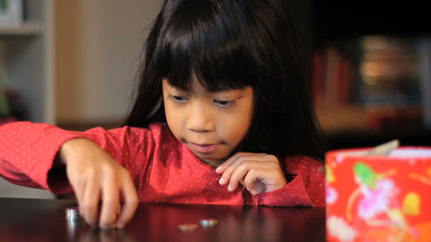 Excited Six Year Old Asian Girl Counts Her Money Stock Video Footage