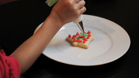 Girl Adding Green Icing To Christmas Cookie Stock Video Footage