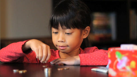 Happy Six Year Old Asian Girl Counting Money Stock Video Footage