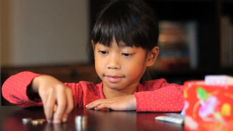 Happy Six Year Old Asian Girl Counting Money Footage