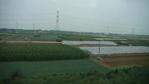 Villages plains tree crops farmland in rural countryside.Speeding train travel,s Footage