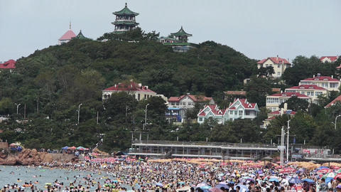 A lot of people at crowded bathing beach.China's Qingdao City.forest island Footage