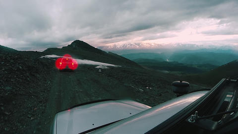 Car rides from the mountain along a dangerous road on a cloudy day. Auto travel Live Action