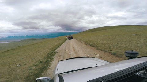 SUV rides a valley with mountains on the horizon. Auto travel: POV - Point of Footage