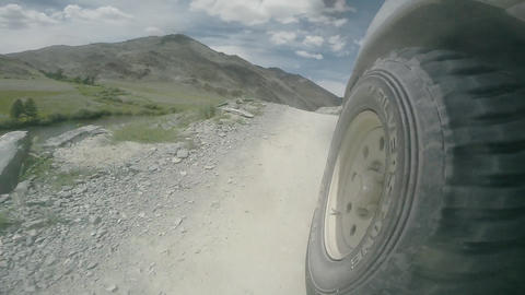 View of the wheel of a car traveling along a valley. Car travels fast on a Footage