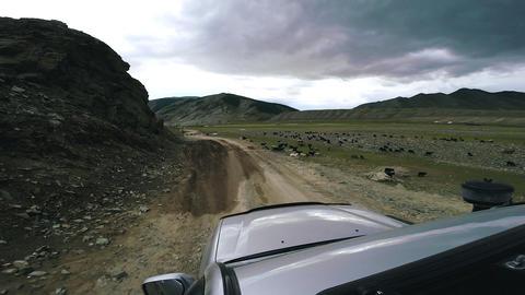 SUV rides over a mountain river on a high mountain road. Wild animals run across Live Action