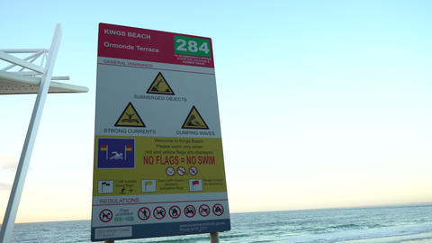 Beach warning sign during sunris, Live Action