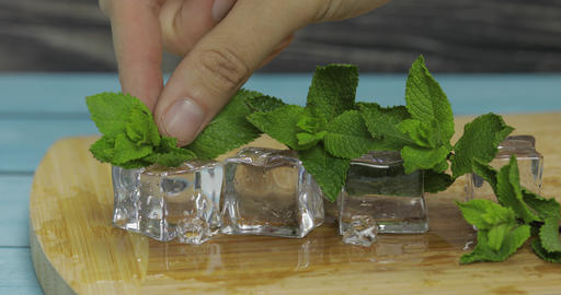 Ice cubes and mint leaves isolated on wooden cutting board Footage
