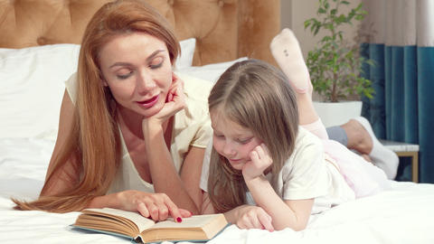 Adorable little girl learning reading at home with her mother Footage