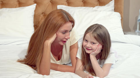 Mother and daughter smiling to the camera, lying on bed together Live Action