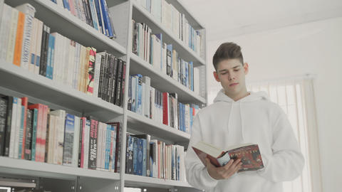 Student reading book in school library. Study lessons for exam Footage