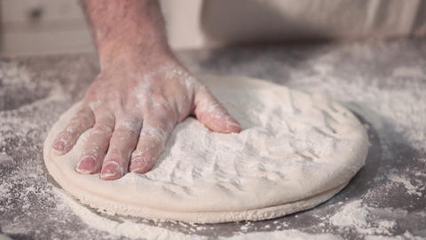 Baker preparing a round bread dough, rotating and kneading the dough Footage