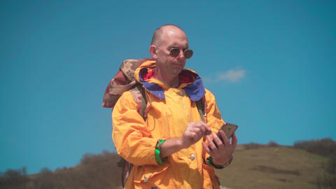 A man in a yellow jacket and glasses stands in mountains, enjoying the scenery Live Action