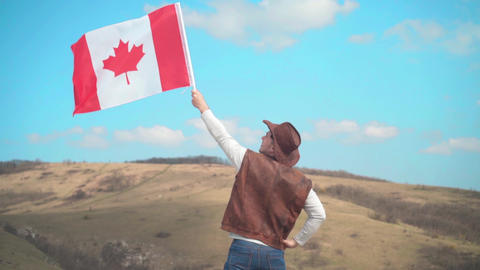 A man in a hat, vest and leather jacket and jeans holds a Canadian flag. A man Footage