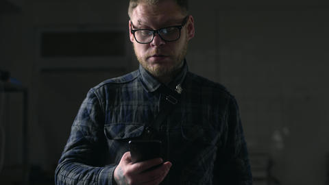 Man in glasses looks carefully to his phone in the dark environment, people with Live Action