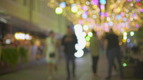 Unknown couple walking along illuminated pedestrian street in the evening Footage